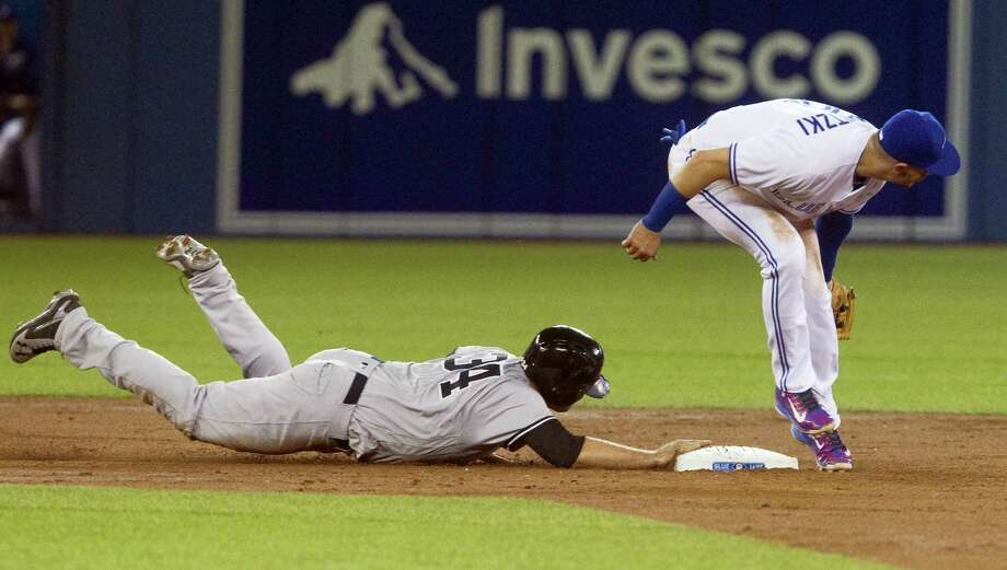 Brian McCann dives back to second base on a pick-off throw on Tuesday. Photo: Fred Thornhill — The Canadian Press Via AP   / The Canadian Press