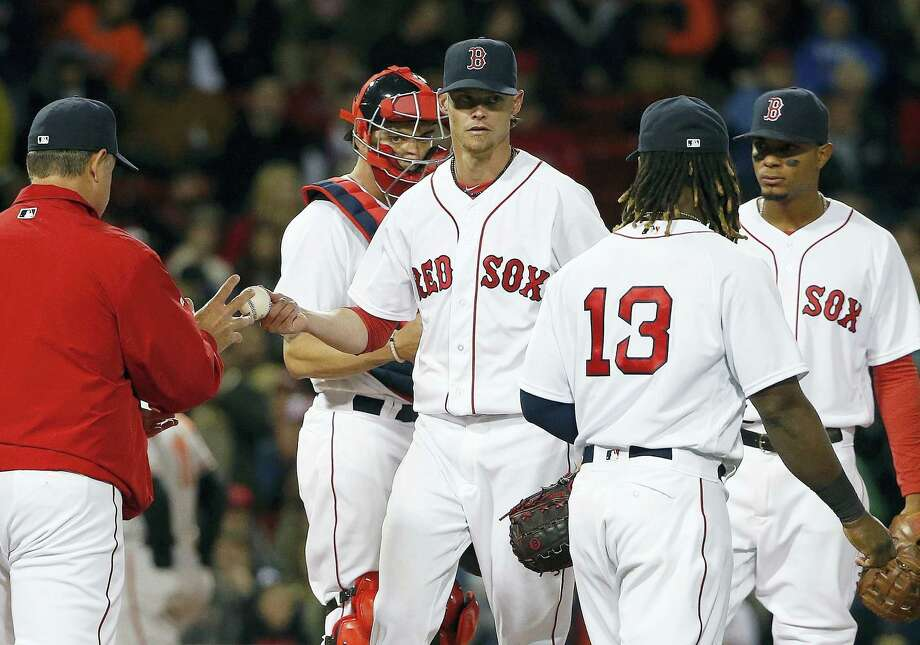Clay Buchholz, center, hands the ball to manager John Farrell during the sixth inning Tuesday. Photo: Michael Dwyer — The Associated Press    / Copyright 2016 The Associated Press. All rights reserved. This material may not be published, broadcast, rewritten or redistributed without permission.