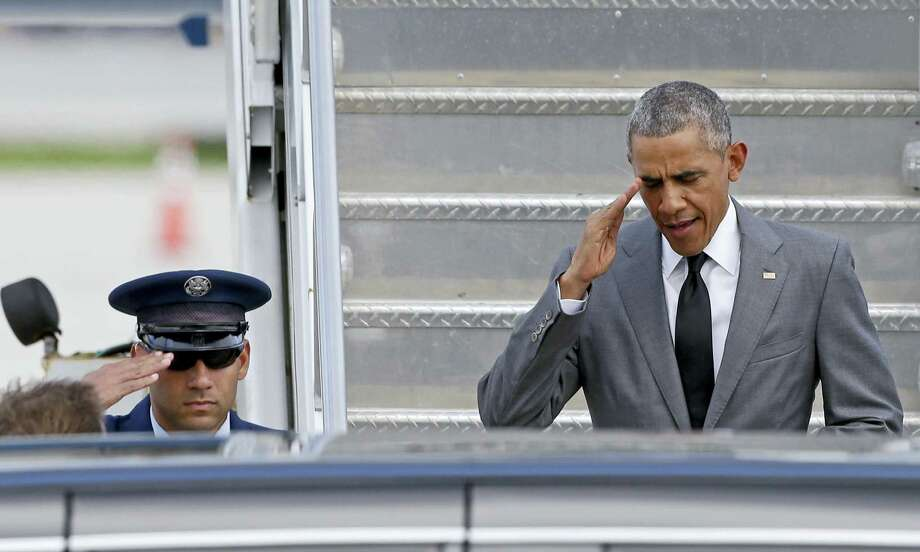 President Barack Obama salutes as he walks down the stairs of Air Force One at his arrival at Miami International Airport in Miami Friday. Photo: ASSOCIATED PRESS   / Copyright 2016 The Associated Press. All rights reserved. This material may not be published, broadcast, rewritten or redistribu