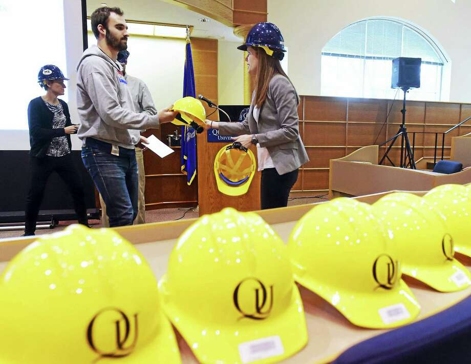 Peter Hvizdak — New Haven Register  Quinnipiac University mechanical engineering sophomore Nik (CQ) Griswold, left, receives his hardhat from mechanical engineering professor Mary Phillips on January 29, 2016 during a ceremony recognizing 102 Quinnipiac Engineering students during the engineering departments second annual Hard Hat Ceremony at the Mount Carmel Auditorium in the Center for Communications and Engineering at the university. Photo: ©2016 Peter Hvizdak / ©2016 Peter Hvizdak