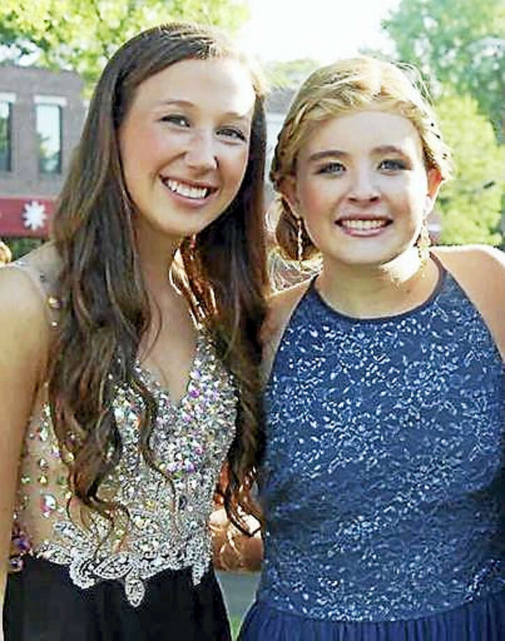 In this May 29, 2015 photo provided by Bonnie Hourican, her daughter Lauren Hourican, left, poses with  Catherine Malatesta before the junior prom at Arlington High School in Arlington, Mass. After Catherine died from a rare cancer on Aug. 2, 2015, some of Catherine's friends, including Lauren, decided to wear her gown to their own proms in 2016 in Catherine's honor. Photo: Bonnie Hourican Via AP    / Bonnie Hourican
