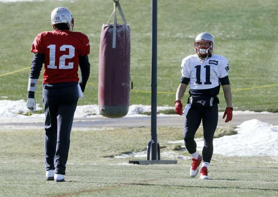 Patriots quarterback Tom Brady (12) and wide receiver Julian Edelman (11) warm up during practice on Thursday. Photo: Steven Senne — The Associated Press   / AP