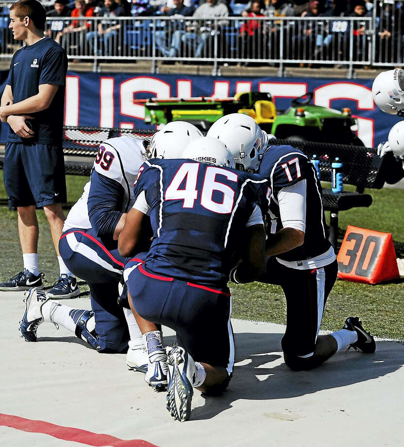 Connecticut's Sean Marinan, left, Marquiese Vann, center, and Bobby Puyol, right, kneel together before during UConn's Blue-White spring game at Rentschler Field last April 11. Marinan will be a scholarship player for this year's spring game. Photo: The Associated Press   / AP2015