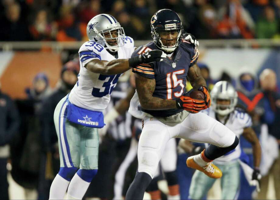 Chicago Bears wide receiver Brandon Marshall (15) makes a catch under pressure from Dallas Cowboys cornerback Brandon Carr (39) during the first half of an NFL football game on Dec. 9, 2013 in Chicago. Photo: AP Photo/Charles Rex Arbogast   / AP