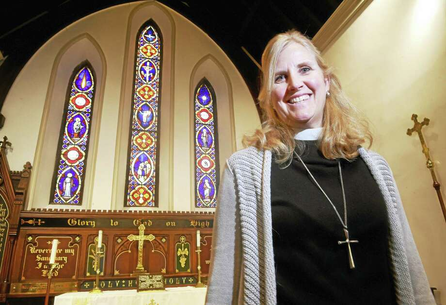 The Rev. Cynthia Knapp is photographed in front of the some of the stained-glass windows slated for restoration at St. Peter's Episcopal Church in Milford. Photo: Arnold Gold — New Haven Register