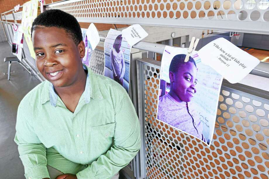 """Perryon Ward, 11, is photographed next to his portrait with his statement, """"I like how a lot of kids play outside,"""" concerning his thoughts about Newhallville at King/Robinson Magnet School in New Haven Monday. Photo: Arnold Gold — New Haven Register"""