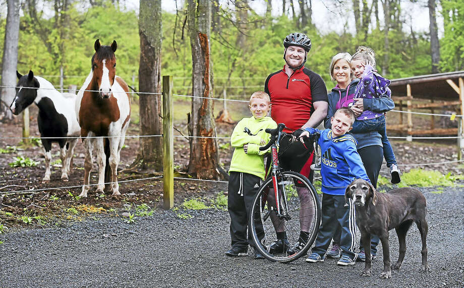 Ryan Walton with his wife, Courtney, and children Charlie, 9, left, Sam, 6, and Hannah, 4, on their farm in Wallingford. Photo: Catherine Avalone — New Haven Register     / New Haven RegisterThe Middletown Press