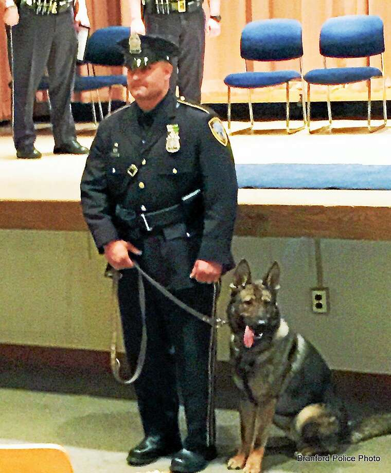 Branford Police Department Officer Luigi Amasino stands with his police dog, Joker. Photo: FILE PHOTO