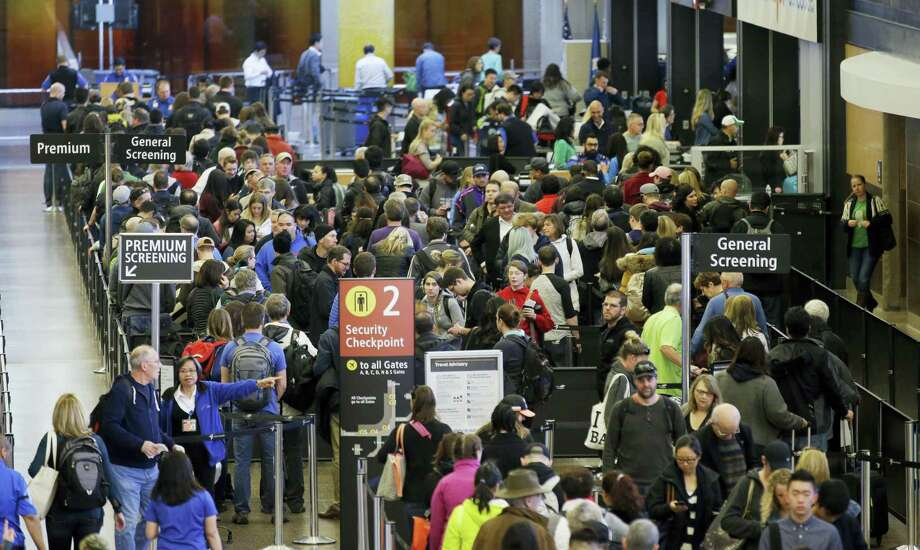 In this March 17, 2016, file photo, travelers wait in line for security screening at Seattle-Tacoma International Airport in Seattle. Two U.S. senators say the way to reduce long airport security lines this summer is for airlines to drop their fees on checking luggage. Massachusetts Democrat Edward Markey and U.S. Sen. Richard Blumenthal said Tuesday, May 10, 2016, they asked executives at 12 airlines to drop checked-bag fees this summer. The senators say suspending the fees won't eliminate lines but it's a start. Photo: AP Photo — Ted S. Warren, File / Copyright 2016 The Associated Press. All rights reserved. This material may not be published, broadcast, rewritten or redistribu