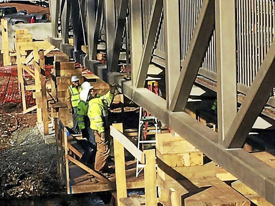 Construction workers from Schultz Corp. in Terryville secure a 50 foot section of a pedestrian bridge into place over the Quinnipiac River in Wallingford. The bridge is part of the third phase of construction of the Quinnipiac River Linear Trail. Photo: Luther Turmelle — New Haven Register