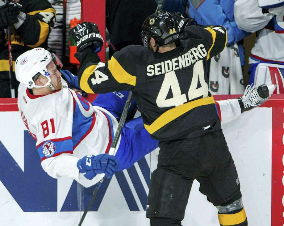 Montreal Canadiens center Lars Eller (81) is knocked off his skates by Boston Bruins defenseman Dennis Seidenberg (44) during the second period of an NHL hockey game Tuesday, Jan. 19, 2016, in Montreal. (Ryan Remiorz/The Canadian Press via AP) Photo: AP / The Canadian Press