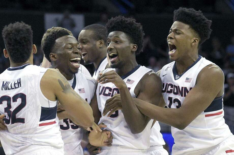 UConn forward Shonn Miller (32), center Amida Brimah (35), guard Daniel Hamilton (5) and forward Steven Enoch (13) celebrate after defeating Memphis 72-58 in the championship game the American Athletic Conference tournament in Orlando, Fla., Sunday. Photo: Phelan M. Ebenhack — The Associated Press   / FR121174 AP