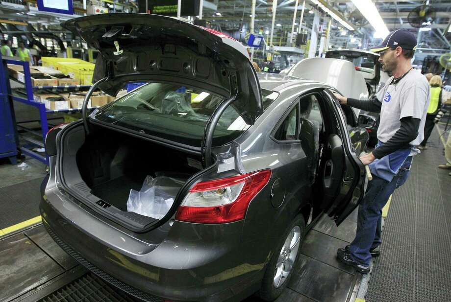 In this Nov. 8, 2012 photo, an assemblyman makes final adjustments to a Ford Focus on the assembly line at the Ford Michigan Assembly Plant in Wayne, Mich. Photo: AP Photo/Carlos Osorio, File   / AP