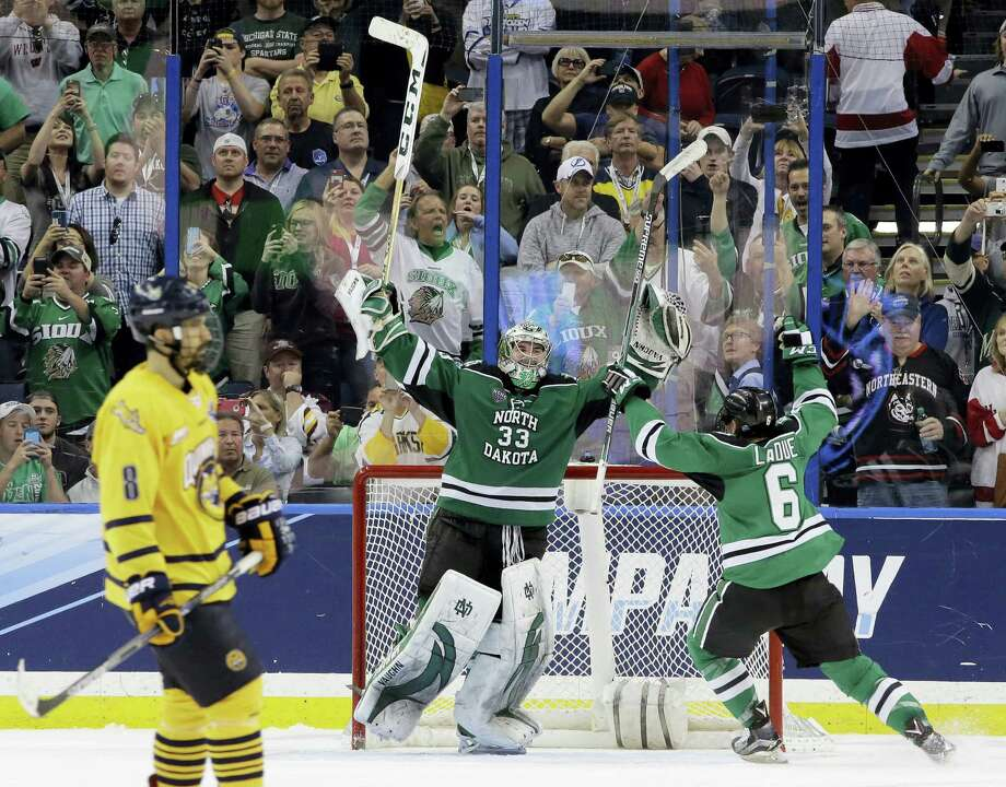 North Dakota goalie Cam Johnson (33) and defenseman Paul LaDue (6) celebrate their 5-1 over Quinnipiac Saturday night at the conclusion of the NCAA Frozen Four championship college hockey game in Tampa, Fla. Photo: Chris O'Meara — The Associated Press   / AP