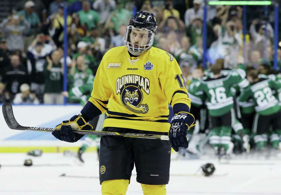 Quinnipiac defenseman Chase Priskie (13) skates off as North Dakota celebrates their 5-1 win during the NCAA Frozen Four championship college hockey game Saturday in Tampa, Fla. Photo: Chris O'Meara — The Associated Press   / AP