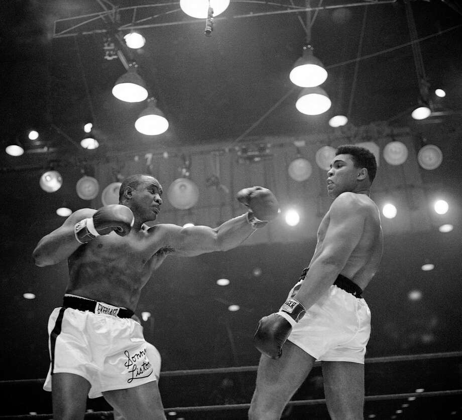 Muhammad Ali (Cassius Clay) uses a variety of bobbing and weaving to stay clear of the left arm of Sonny Liston in their title fight in Miami Beach, Fla. in 1964.  Ali, the magnificent heavyweight champion whose fast fists and irrepressible personality transcended sports and captivated the world, has died according to a statement released by his family Friday, June 3, 2016. He was 74. Photo: AP Photo / AP