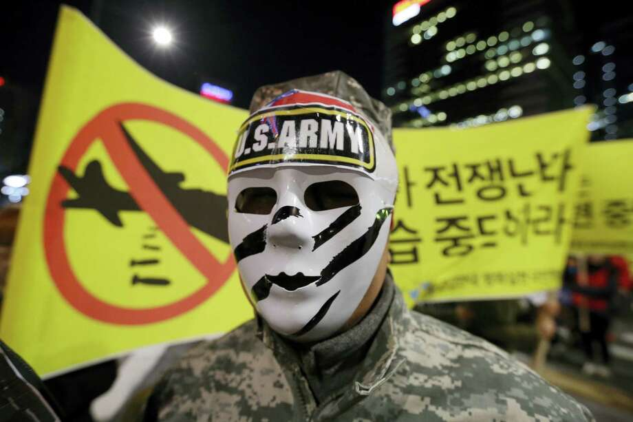 """A South Korean protester wearing a mask marches toward the U.S. Embassy during a rally opposing the joint military exercises, dubbed Key Resolve and Foal Eagle, between the U.S. and South Korea in Seoul, South Korea on March 11, 2016. North Korea responded Thursday to new sanctions from South Korea by firing short-range ballistic missiles into the sea in a show of defiance and vowing to """"liquidate"""" all remaining South Korean assets at former cooperative projects in the North. The letters read """" Stop the joint military exercises between the U.S. and South Korea"""". Photo: AP Photo/Ahn Young-joon   / AP"""