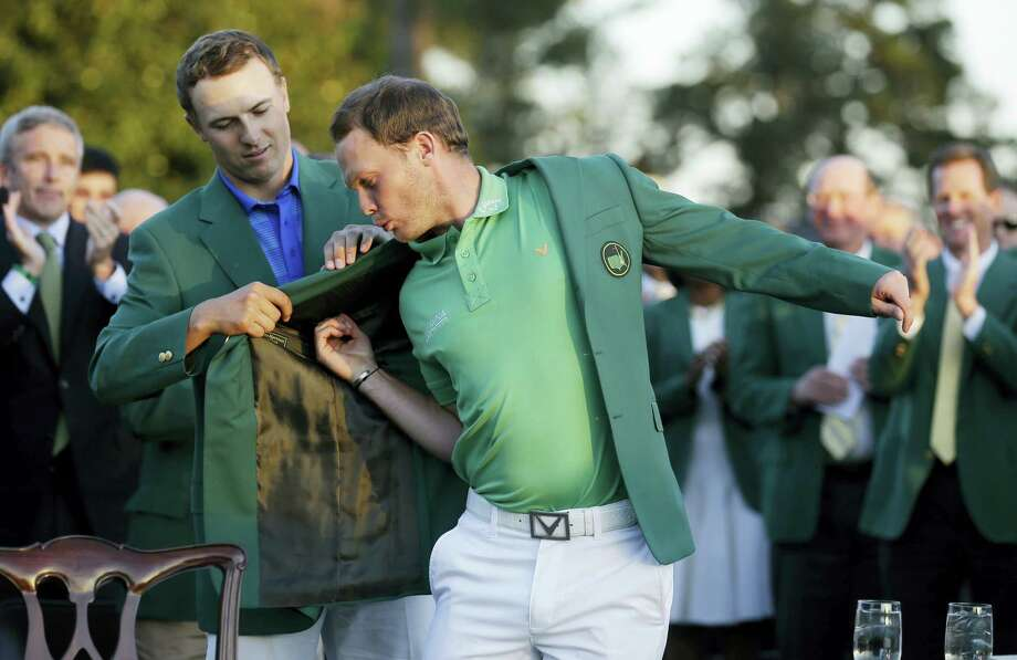 Defending champion Jordan Spieth, left, helps 2016 Masters champion Danny Willettput on his green jacket following the final round of the Masters Sunday. Photo: Chris Carlson — The Associated Press   / AP