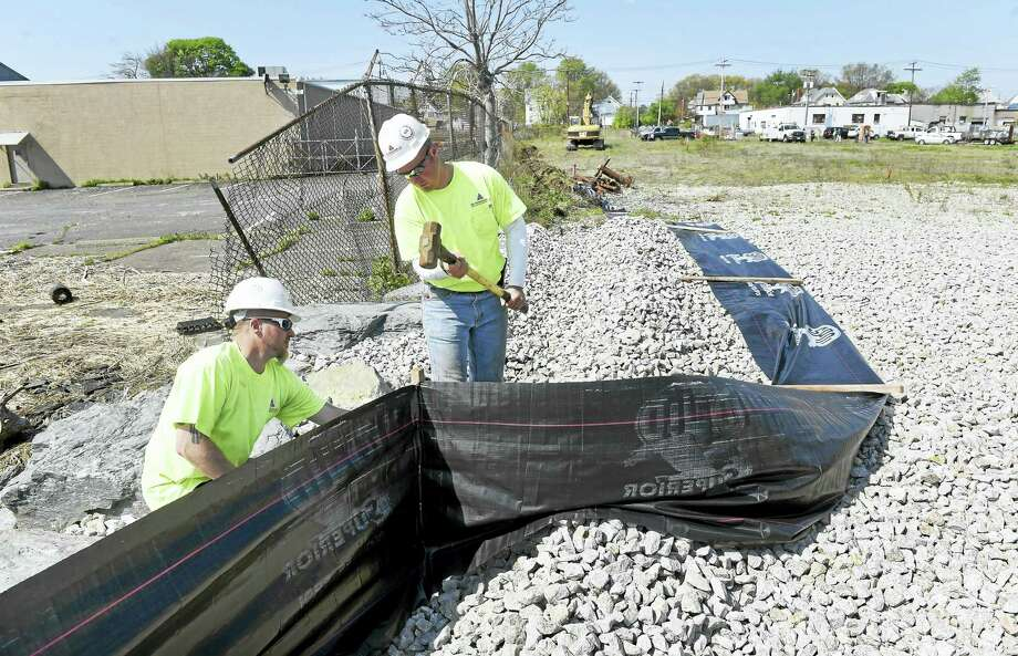 John Cuscovitch, left, and Andrew Plante install a silt fence for erosion control at 105 Water St. in West Haven on property that will be part of The Haven. Photo: Arnold Gold — New Haven Register