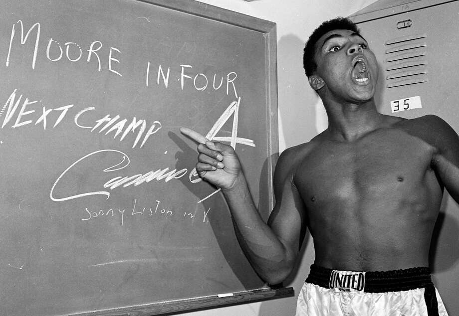 Young heavyweight boxer Cassius Clay, who later changed his name to Muhammad Ali, points to a sign he wrote on a chalk board in his dressing room before his fight against Archie Moore in Los Angeles. Photo: The Associated Press File Photo   / AP1962