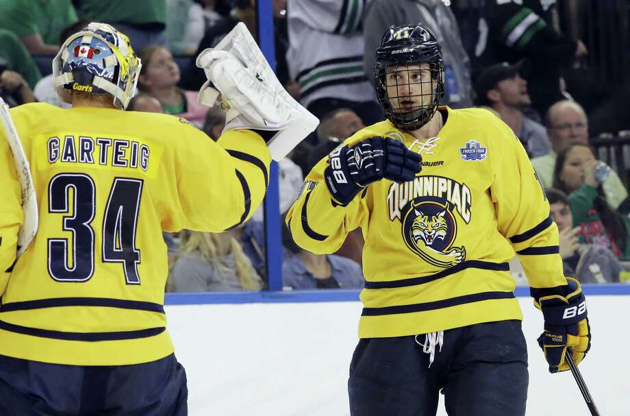 Quinnipiac forward Tim Clifton (11) celebrates his goal against North Dakota with goalie Michael Garteig during the first period of the NCAA Frozen Four championship game Saturday. Photo: Chris O'Meara — The Associated Press   / AP