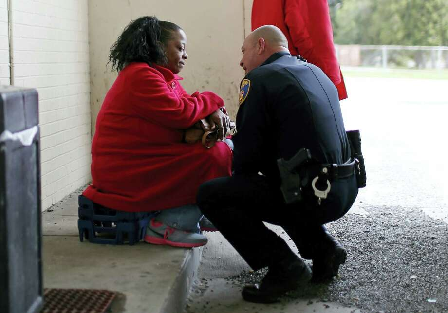 In this April 8, 2016 photo, Baltimore Police Department Officer Ken Hurst, right, consoles Rosa Brown, who was expressing suicidal thoughts following the recent death of her son, during his foot patrol in Baltimore. Hurst is one of 450 police officers who are part of a foot patrol program aimed at getting police officers out of their cars and onto the streets of Baltimore's most dangerous neighborhoods, not to make arrests but to make friends. Photo: AP Photo/Patrick Semansky   / Copyright 2016 The Associated Press. All rights reserved. This material may not be published, broadcast, rewritten or redistributed without permission.