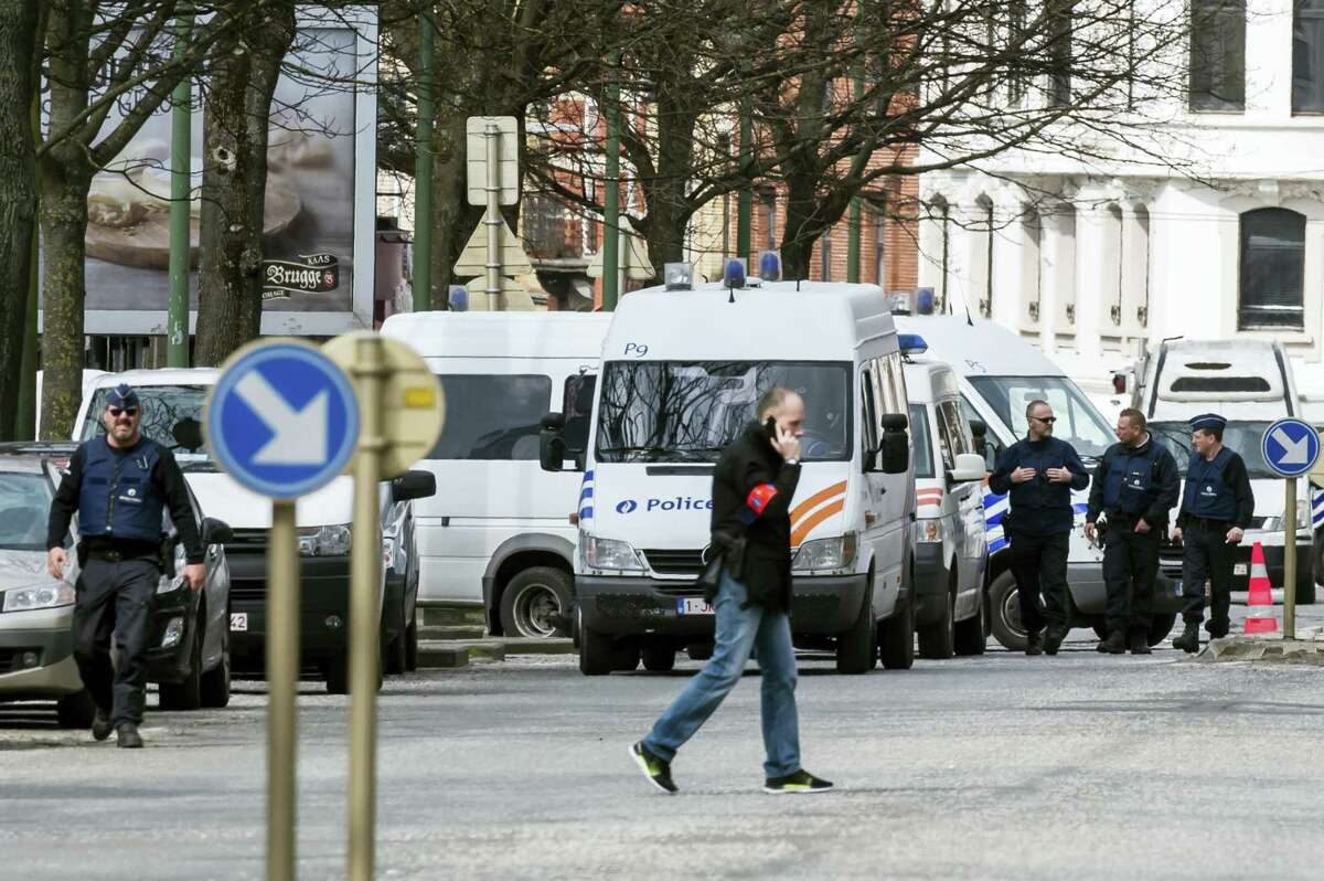 Police secure an area during a house search in the Etterbeek neighborhood in Brussels on y April 9, 2016. The arrest Friday of six men suspected of links to the Brussels bombings, including the last known fugitive in last year's Paris attacks, raised new questions about the extent of the Islamic State cell believed to have carried out the intertwined attacks that left 162 people dead in two countries.