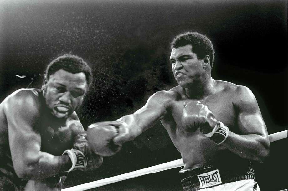 In this Oct. 1, 1975, file photo, Heavyweight champion Muhammad Ali connects with a right against challenger Joe Frazier in the ninth round of their title fight in Manila, Philippines.   Ali won the fight on a decision to retain the title. Ali, the magnificent heavyweight champion whose fast fists and irrepressible personality transcended sports and captivated the world, has died according to a statement released by his family Friday, June 3, 2016. He was 74. Photo: AP Photo/Mitsunori Chigita    / AP