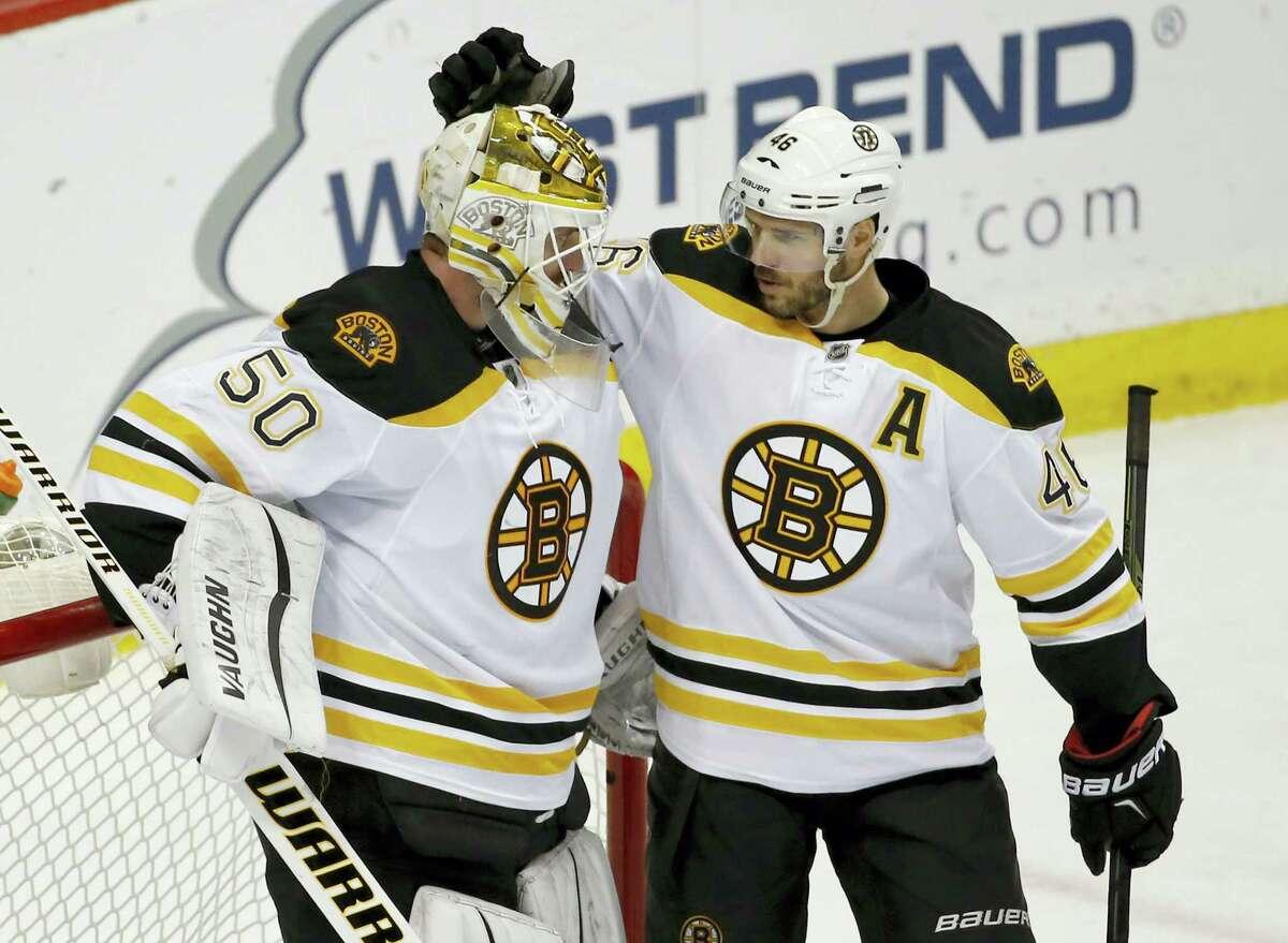 Boston Bruins center David Krejci (46), of the Czech Republic, congratulates Bruins goalie Jonas Gustavsson (50), of Sweden, after they defeated the Minnesota Wild 4-2 in an NHL hockey game in St. Paul, Minn., Saturday, Feb. 13, 2016. (AP Photo/Ann Heisenfelt)