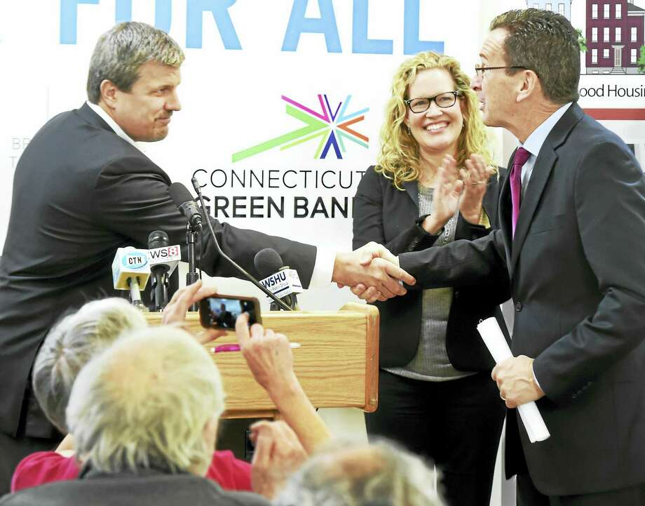 Connecticut Gov. Dannel P. Malloy, right, shakes hands with PosiGen CEO Tom Neyhart at New Haven Neighborhood Services in New Haven Wednesday. At center is PosiGen Vice President of Business Development & Government Relations Elizabeth Galante. Photo: Peter Hvizdak — New Haven Register    / ©2016 Peter Hvizdak
