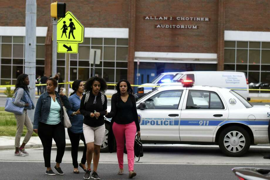 Parents and students walk across the street from the campus of High Point High School in Beltway, Md., Thursday, May 5, 2016. A man shot and killed a woman who was waiting to pick up her children in the parking lot of the suburban Washington high school Thursday and wounded a man who tried to intervene, police said. (Michael Robinson Chavez/The Washington Post via AP) Photo: AP / The Washington Post