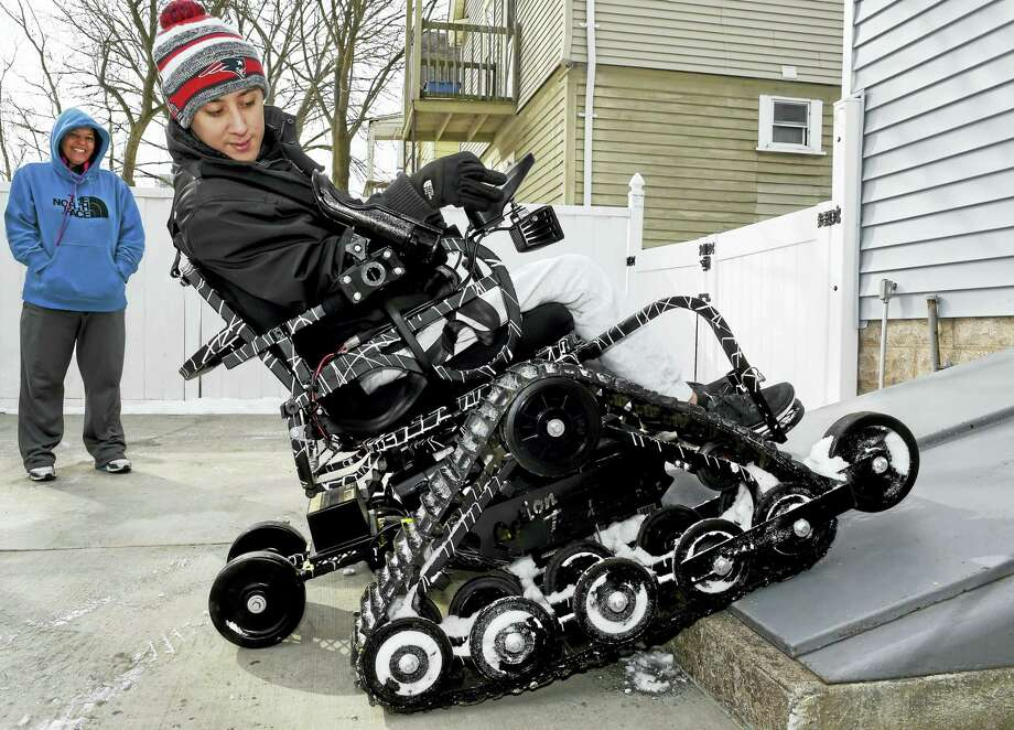 (Peter Hvizdak - New Haven Register)  Sean Pesce, 23, a former Army Ranger who was severely wounded in Afghanistan and lost the use of his legs, uses an Action Trackstander, a customized and treaded all-terrain vehicle as his mother, Gail Pesce, watches him maneuver at their West Haven home Friday. The Action Trackstander allows him to maneuver over difficult obstacles, enabling him to participate in many outdoor activities, like hunting and fishing,  that he otherwise would not be able to do while using a standard wheelchair. Photo: ©2016 Peter Hvizdak / ©2016 Peter Hvizdak