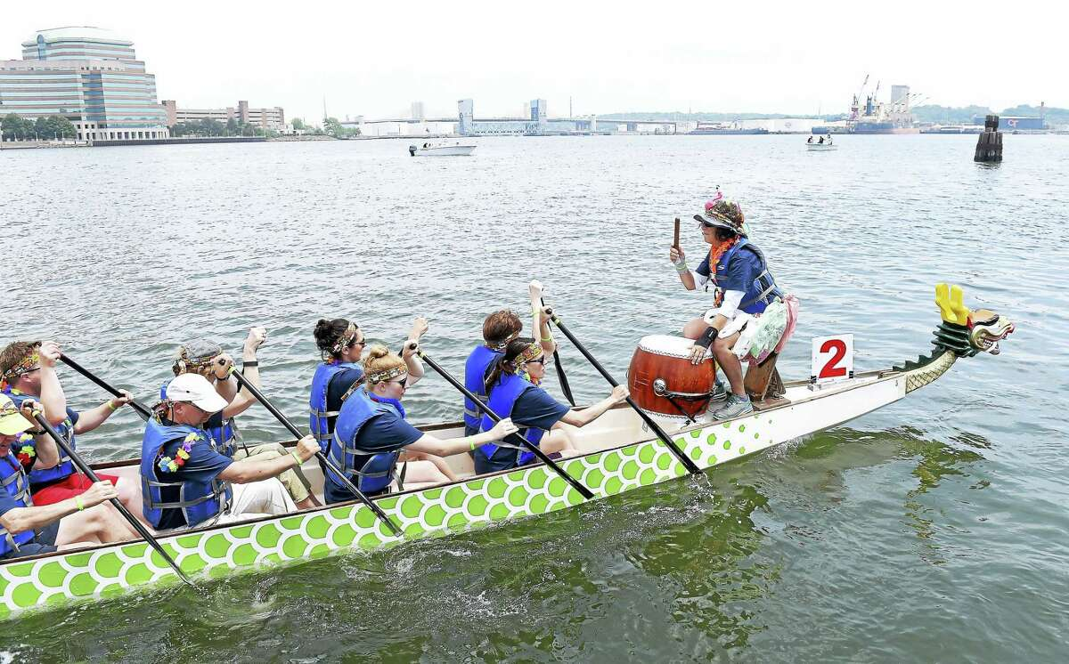 The Boathouse OARchitects led by drummer Judy Clark, right, head into position during the Dragon Boat Regatta near the Long Wharf Pier in New Haven Saturday, June 4, 2016. The Boathouse Oarchitects are from the architectural firm, Gregg, Wies and Gardner Architects.