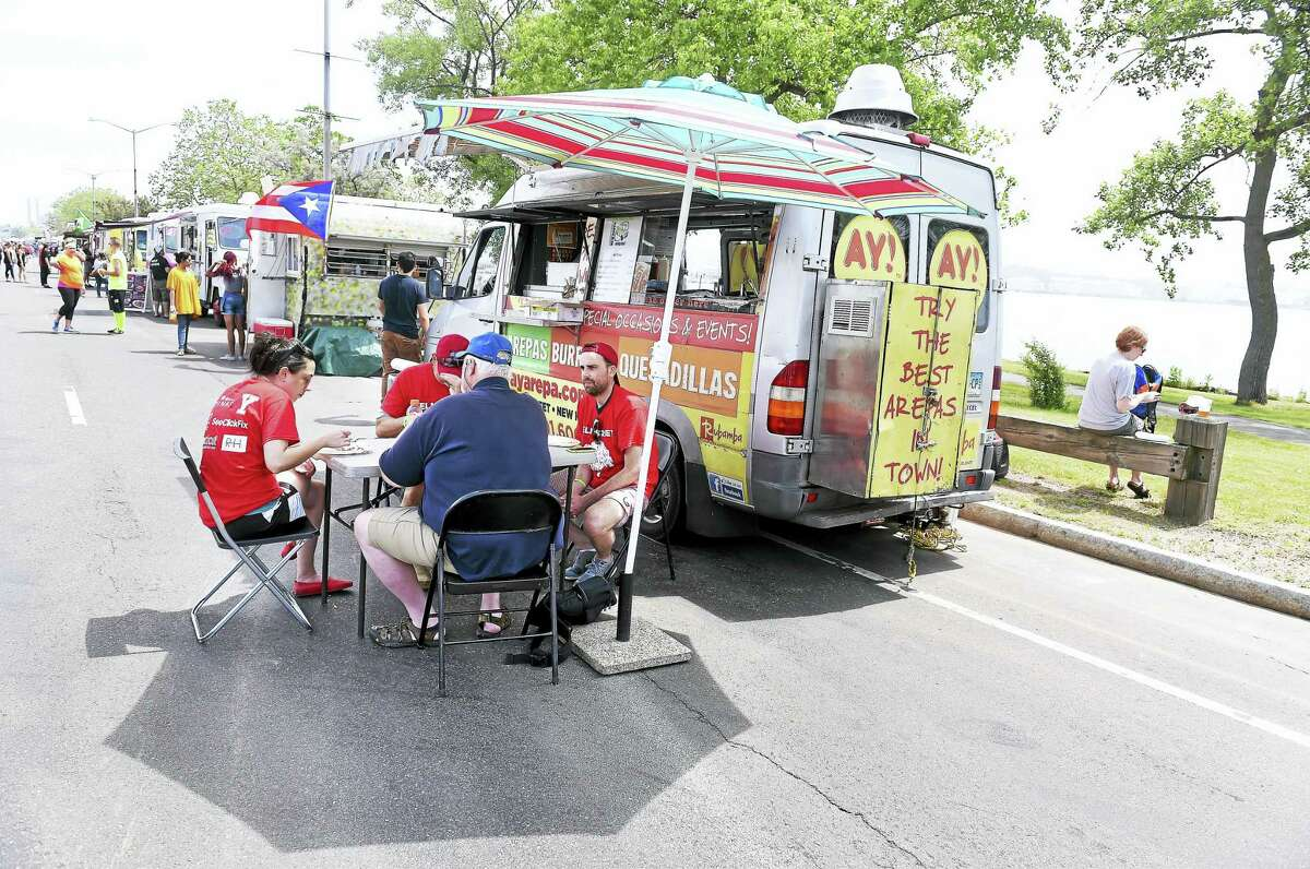Competitors from the Dragon Boat Regatta eat at the food truck, AY! Arepa, on Long Wharf Drive in New Haven during the New Haven Food Truck Festival Saturday, June 4, 2016.