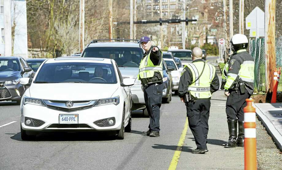 New Haven Police Officer Scott Durkin, center, directs a car to be ticketed for distracted driving on North Frontage Road in New Haven last month. Photo: Arnold Gold — New Haven Register