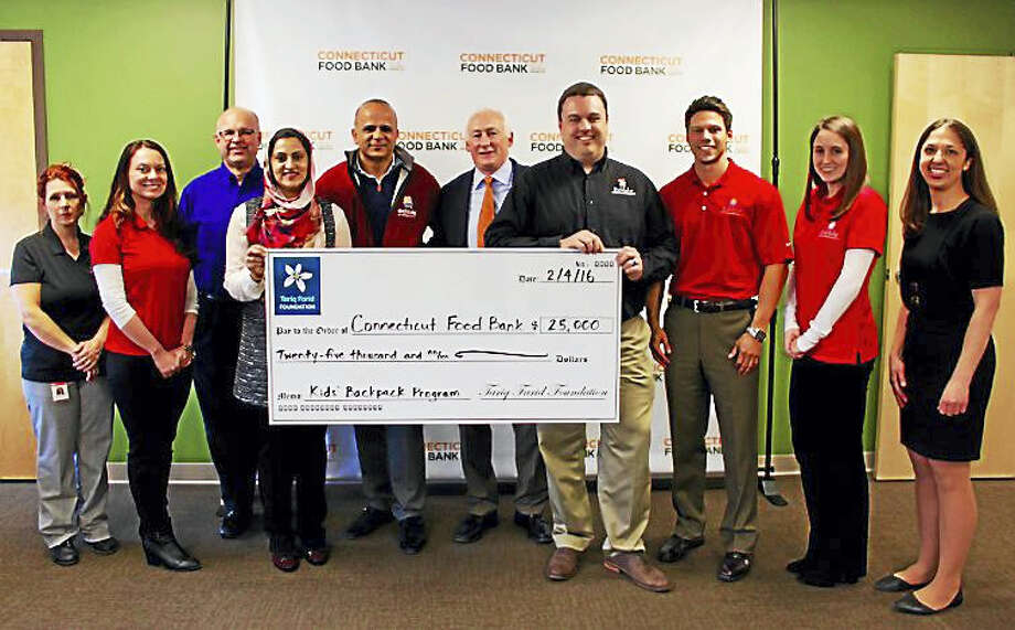 Tariq and Asma Farid (fifth and fourth from left) are joined by Edible Arrangements employees as they present a check to Connecticut Food Bank interim CEO Paul O'Leary (sixth from left) in support of the Kids' BackPack program. Photo: CONTRIBUTED PHOTO