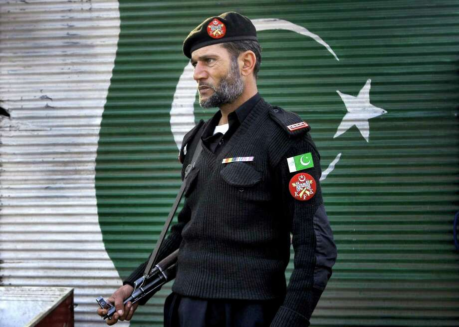 A police officer stands guard close to the site of a suicide attack, in Peshawar, Pakistan, Tuesday, Jan. 19, 2016. A suicide attack targeting a police checkpoint in northwestern Pakistan Tuesday killed many people, a local government official said. Photo: AP Photo/Mohammad Sajjad    / AP