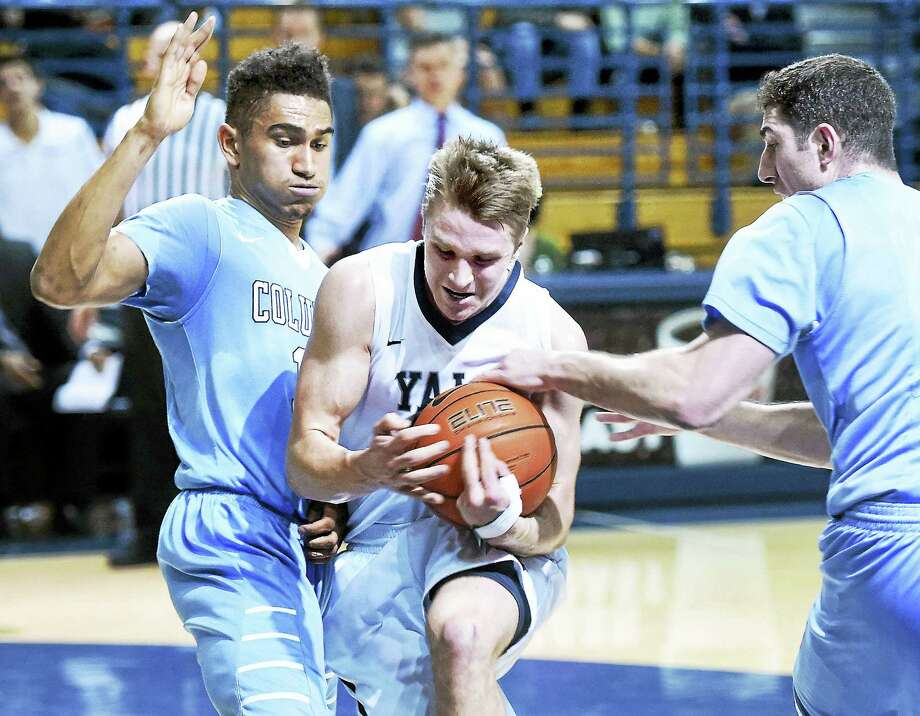 Arnold Gold - Register  Yale's Makai Mason, center, is sandwiched between Columbia's Maodo Lo, left and Alex Rosenberg during Friday's game in New Haven. Photo: Journal Register Co.