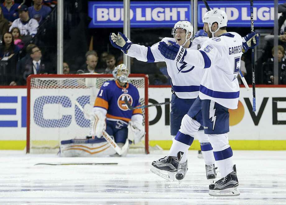 Tampa Bay Lightning defenseman Jason Garrison (5) and left wing Ondrej Palat (18) celebrate after Garrison scored the winning-goal in overtime against New York Islanders goalie Thomas Greiss (1) during the overtime period of Game 4 of the NHL hockey Stanley Cup Eastern Conference semifinals, Friday, May 6, 2016, in New York. The Lightning won 2-1. (AP Photo/Frank Franklin II) Photo: AP / Copyright 2016 The Associated Press. All rights reserved. This material may not be published, broadcast, rewritten or redistribu
