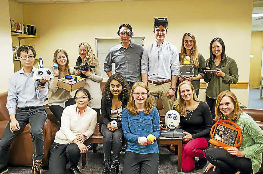 Top row, from left, Beibin Li, holding GoBug prototype, BeatBots LLC; Stephanie Valencia, holding her Sensory Toybox, a device she created to look at sensory profiles in children; Marilena Mademtzi, holding a Microsoft Kinect, representing studies she's conducted with games for children with ASD; Frederick Shic, director, wearing a head-mounted eye tracker created by Adam Naples and Elizabeth Kim; Logan Hart, wearing an Oculus Rift, a virtual reality device; Carla Wall, holding Keepon, a robot created with BeatBots and the Yale Social Robotics Group led by Brian Scassellati; Amy Ahn, holding an EyeTribe, a low-cost eye tracker used to study attention.  Bottom row, from left: Quan Wang, wearing Google glasses; Emon Datta, holding a Sphero robot; Erin Barney, holding more Spheros; Laura Boccanfuso, holding L-E, a robot she designed with the Yale Social Robotics Laboratory and Brandon Hudik for promoting communication in children with ASD, and Claire Foster, holding an iPad used to study social visual attention in children with ASD. On the iPad screen is Patricia Perez, a graduate in Spain working with the team on several studies at TIL. Photo: CONTRIBUTED PHOTO