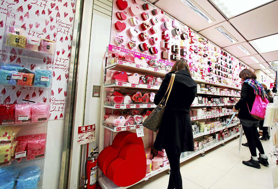 In this Feb. 14, 2012, file photo, women look at heart-shaped boxes containing Valentine's Day chocolates on sale at a store in Tokyo. In Japan, women buy chocolates for men on Valentine's Day, not vice versa. Photo: AP Photo/Shizuo Kambayashi, File    / AP