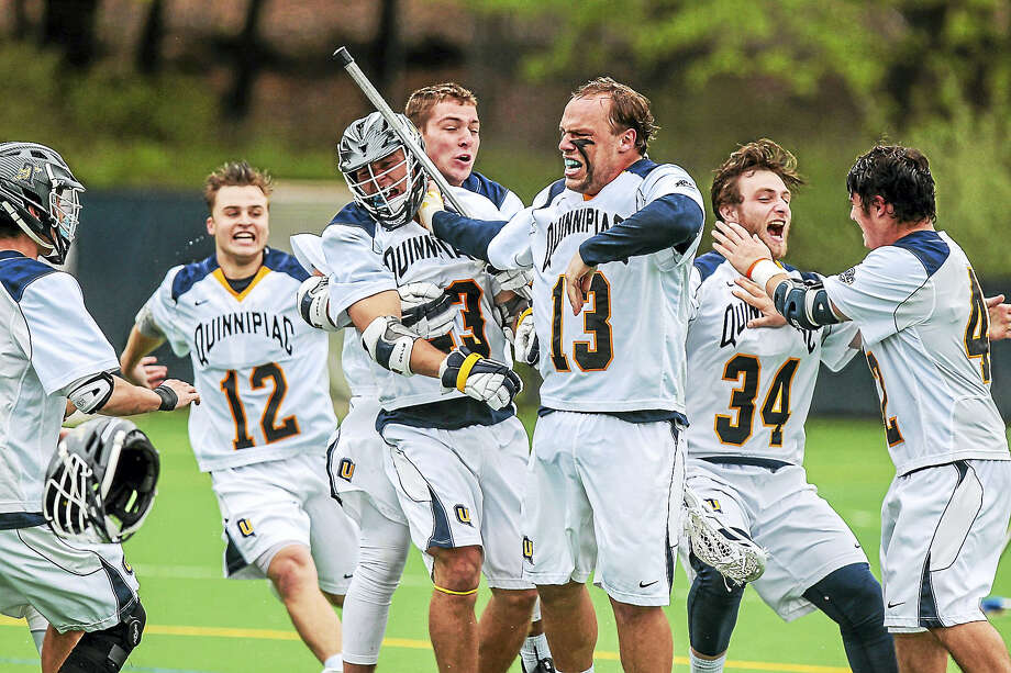 Quinnipiac men's lacrosse goaltender Jack Brust (13) and his teammates celebrate their 13-9 win over Marist in the MAAC tournament championship on Saturday. Photo: John Vanacore — For The Register
