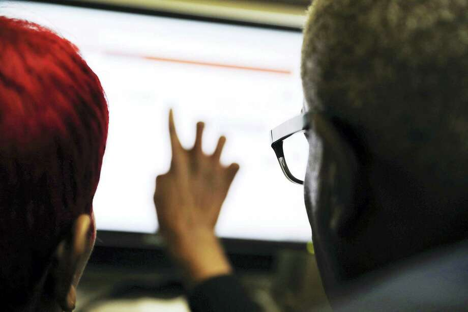 In this Thursday, March 3, 2016, file photo, Georgia Department of Labor services specialist Louis Holliday, right, helps a woman with a job search on a computer at an unemployment office in Atlanta. On Thursday, June 2, 2016, the Labor Department reports on the number of people who applied for unemployment benefits in the previous week. Photo: AP Photo/David Goldman, File    / Copyright 2016 The Associated Press. All rights reserved. This material may not be published, broadcast, rewritten or redistribu