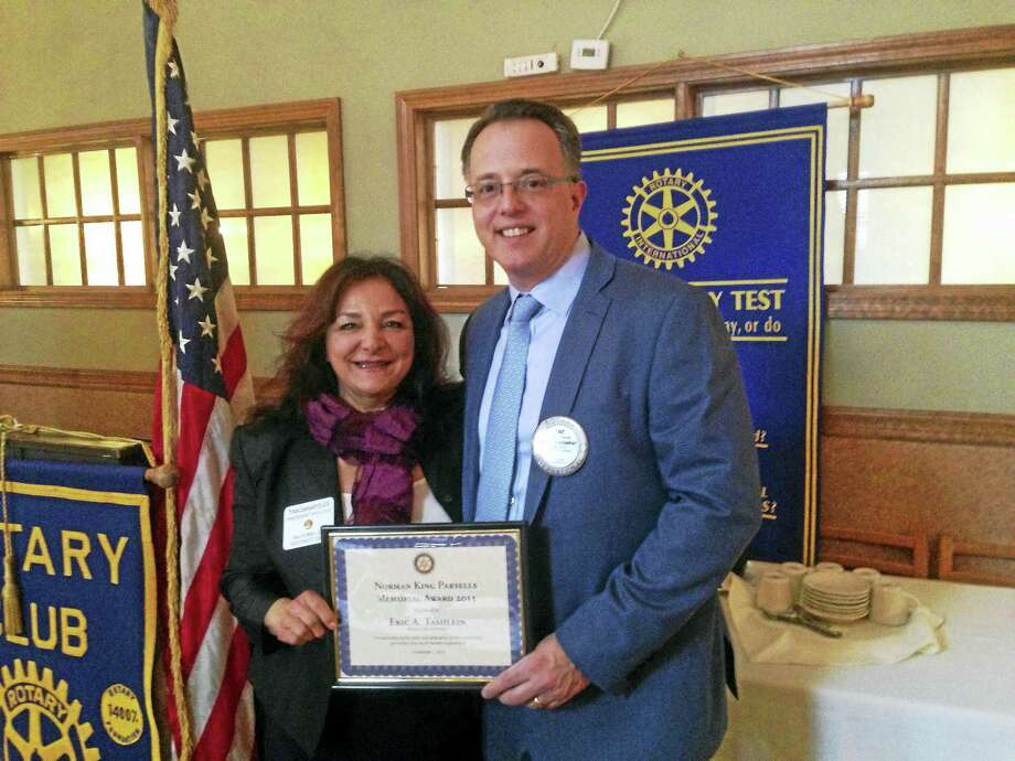 Tina DeNapoles, Milford Rotary Club president, left, presents the Norman K. Parsells Award to former club President Eric A. Tashlein. Photo: CONTRIBUTED PHOTO
