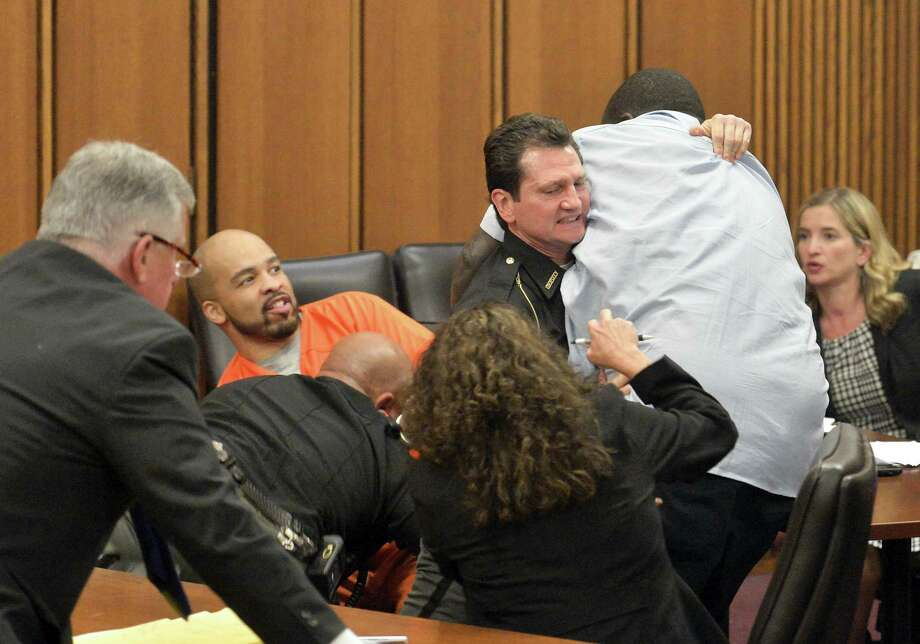 A court officer tackles the father of one of three victims of Ohio serial killer Michael Madison, left, who leaped over a table to attack the defendant in court just minutes after the judge pronounced a death sentence in Cuyahoga County Common Pleas Court Thursday, June 2, 2016, in Cleveland. Photo: AP Photo/David Richard    / FR25496 AP