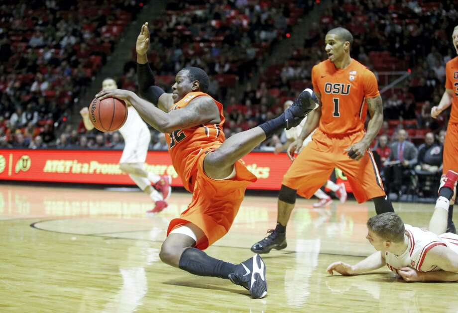 Oregon State forward Jarmal Reid (32) and Utah forward Jakob Poeltl, right foreground, fall during the second half of a game on Sunday in Salt Lake City. Photo: Rick Bowmer — The Associated Press   / AP