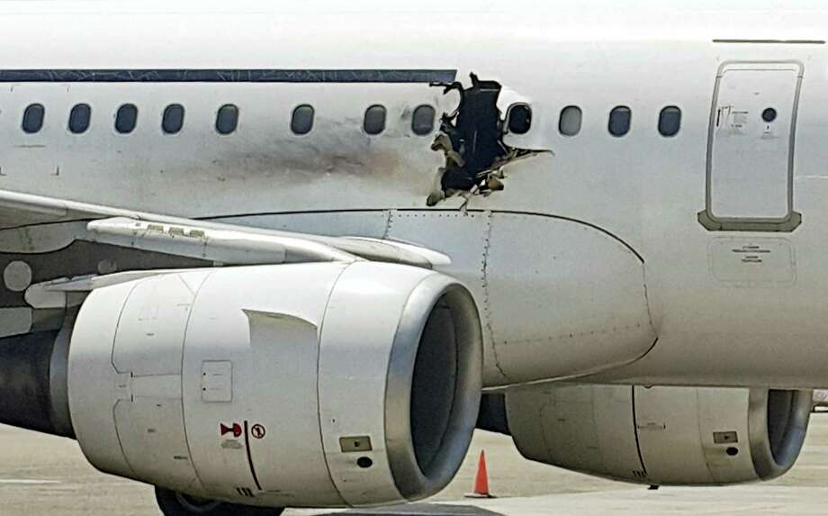 In this Tuesday, Feb. 2, 2016, file photo, a hole is photographed in a plane operated by Daallo Airlines as it sits on the runway of the airport in Mogadishu, Somalia. Photo: AP Photo, File / AP