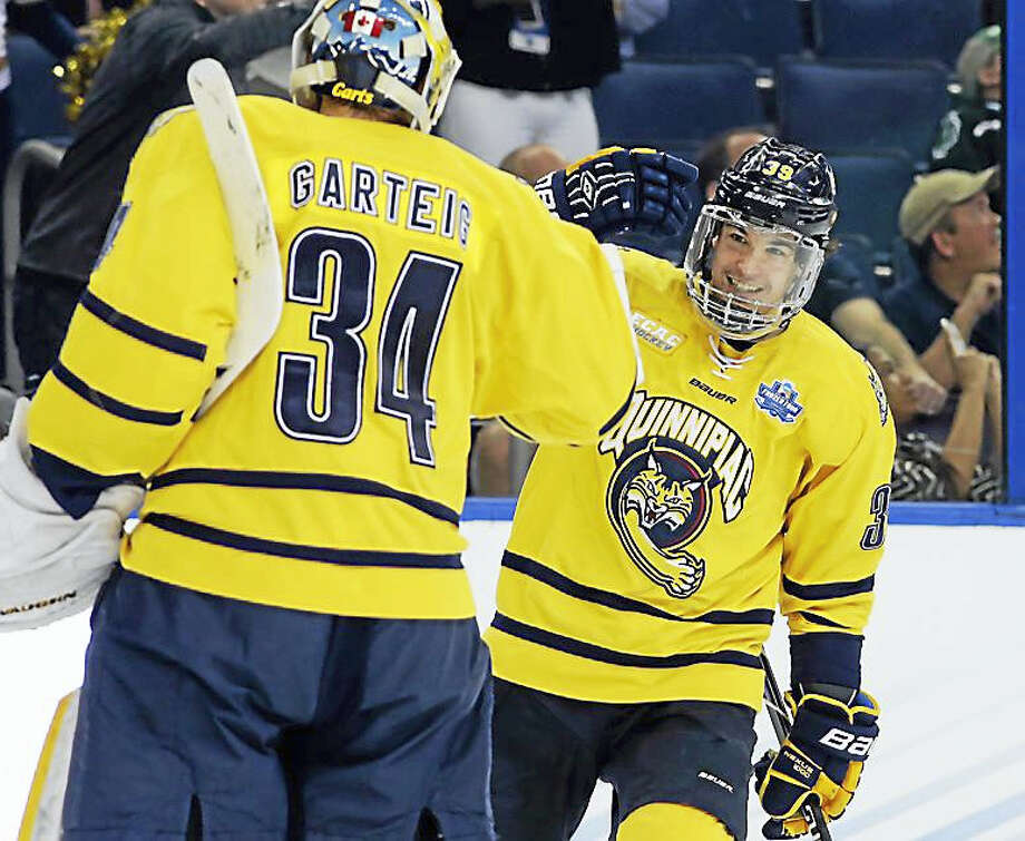 Quinnipiac forward Andrew Taverner (39) celebrates with goalie Michael Garteig after scoring against Boston College during the first period of an NCAA Frozen Four semifinal college hockey game Thursday in Tampa, Florida. Photo: AP Photo/Chris O'Meara
