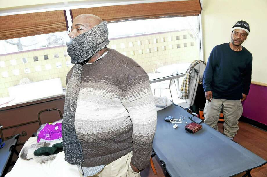 William Wilson (left) and Dion Beall listen to Minister Douglas Kearse (not in photo) talk about his brief experience with homelessness at a warming center inside Church on the Rock in New Haven on 2/13/2016. Photo: ARNOLD GOLD — NEW HAVEN REGISTER
