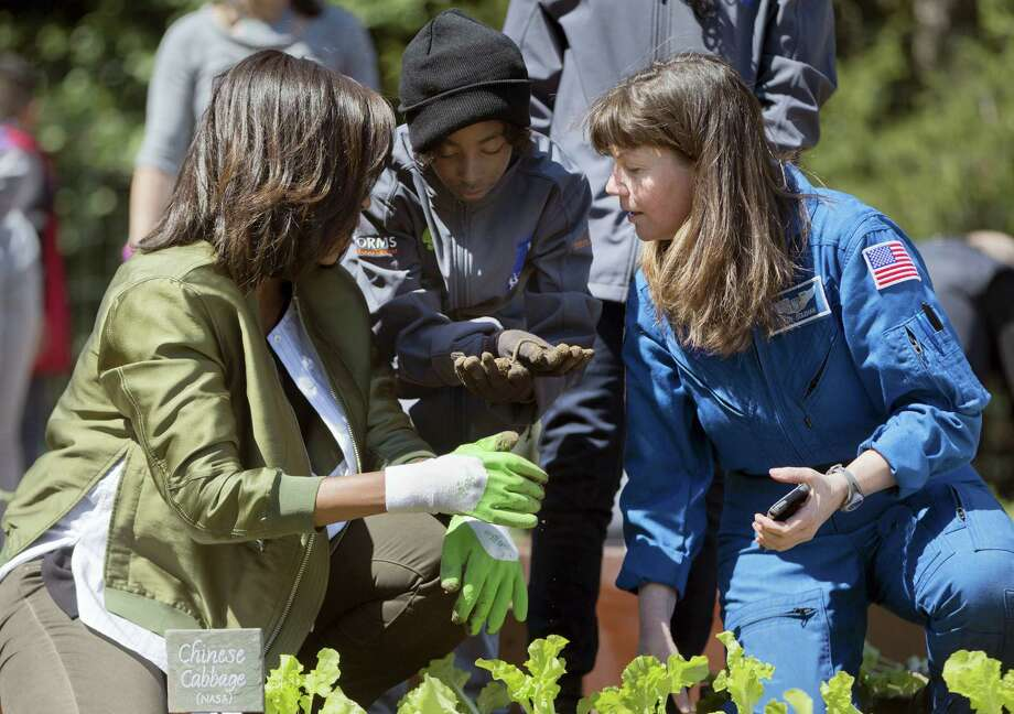 A students from New Orleans shows an earthworm to first lady Michelle Obama, left, and NASA astronaut Cady Coleman, right, while they help plant vegetables during the eight annual White House Kitchen Garden planting on the South Lawn of the White House in Washington on Tuesday. Photo: The Associated Press   / AP